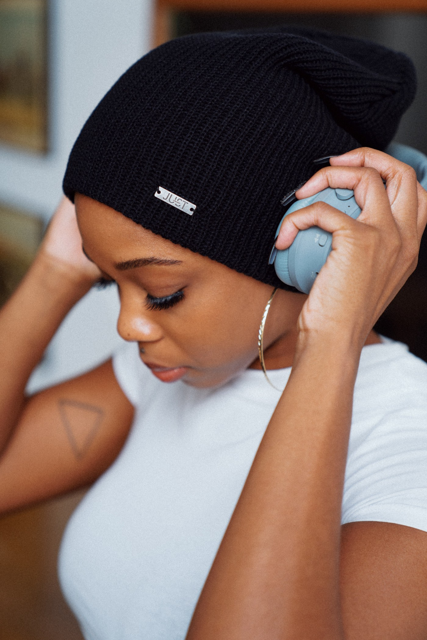 The image shows a pretty black girl covering her ears with a pair of headphones. She apparently is tuning out her surroundings and going within
