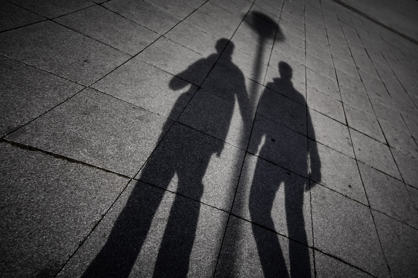 A silhouette of two men holding hands while leaning against a streetlight is projected onto the gray pavement below.