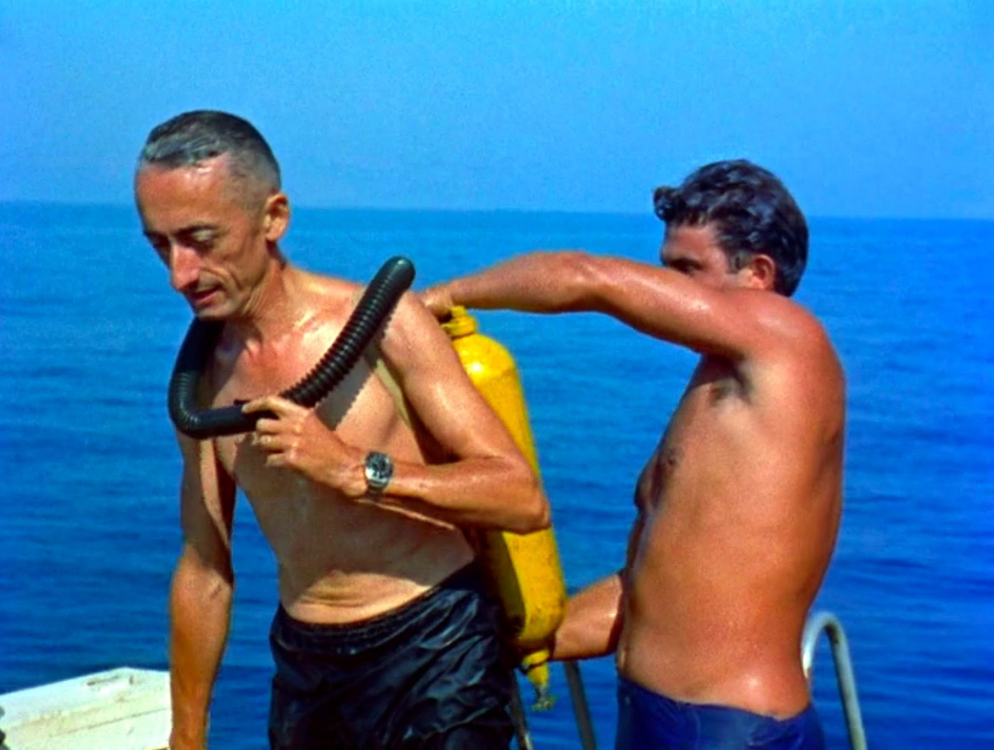 Jacques Cousteau wearing his Aqua-Lung, with his team mate helping him
