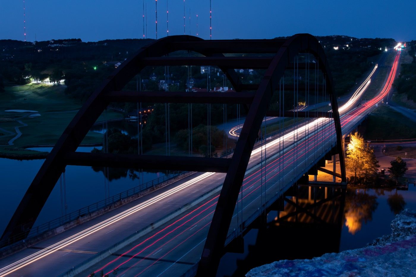 Time lapse of a bridge taken at night, with the lights of passing vehicles forming a continuous glowing line.