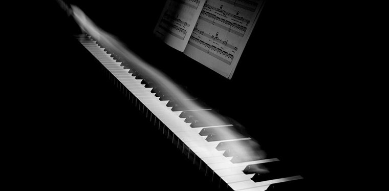 long exposure photo of a hand on a piano