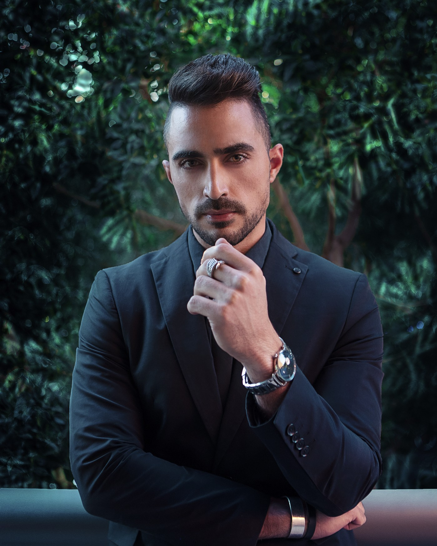 Sleek dressed male with side cuts hairstyle and trimmed beard, wearing blazer, watch, looking into camera determined.