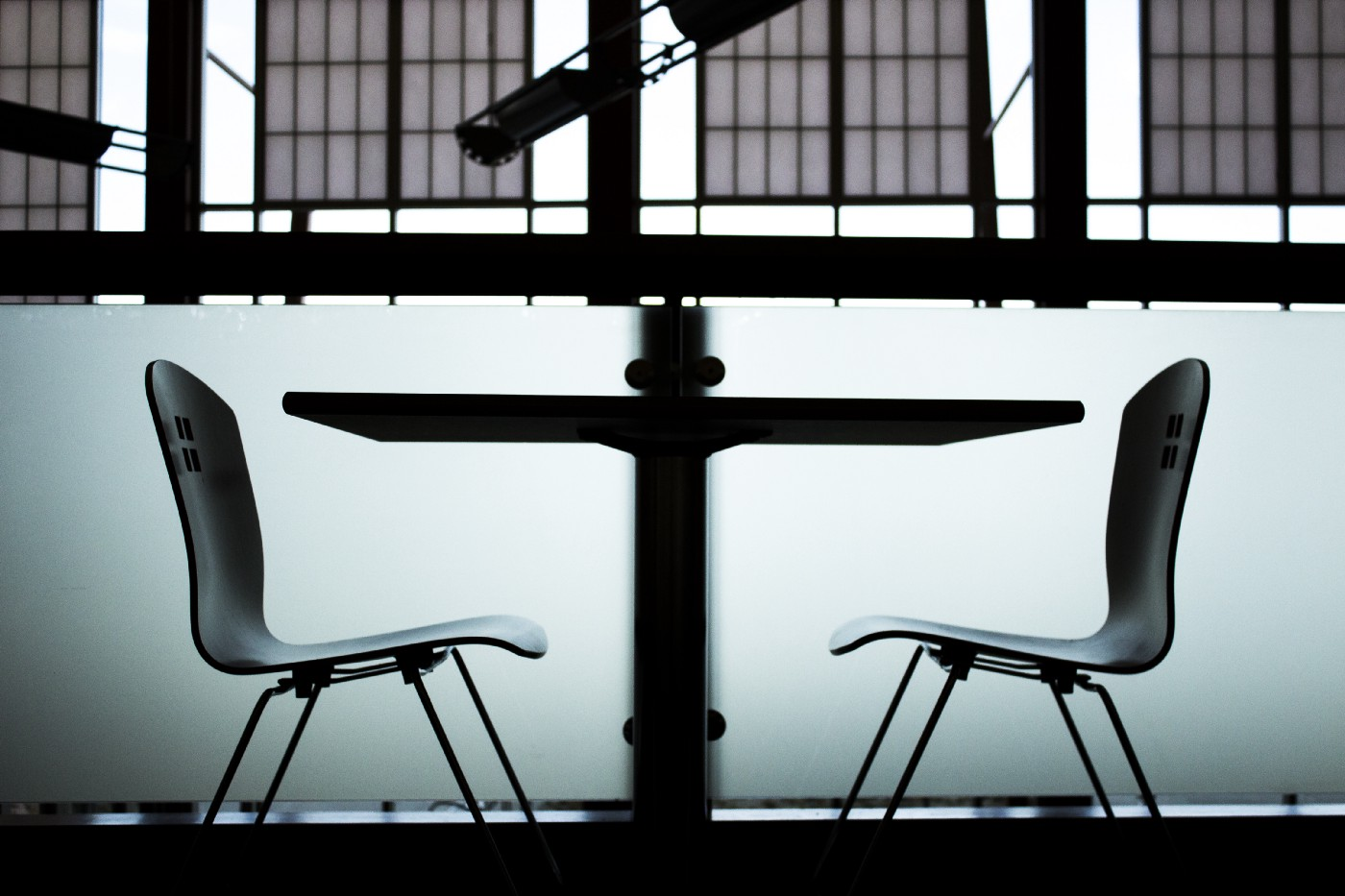 Two chairs at a table facing each other.