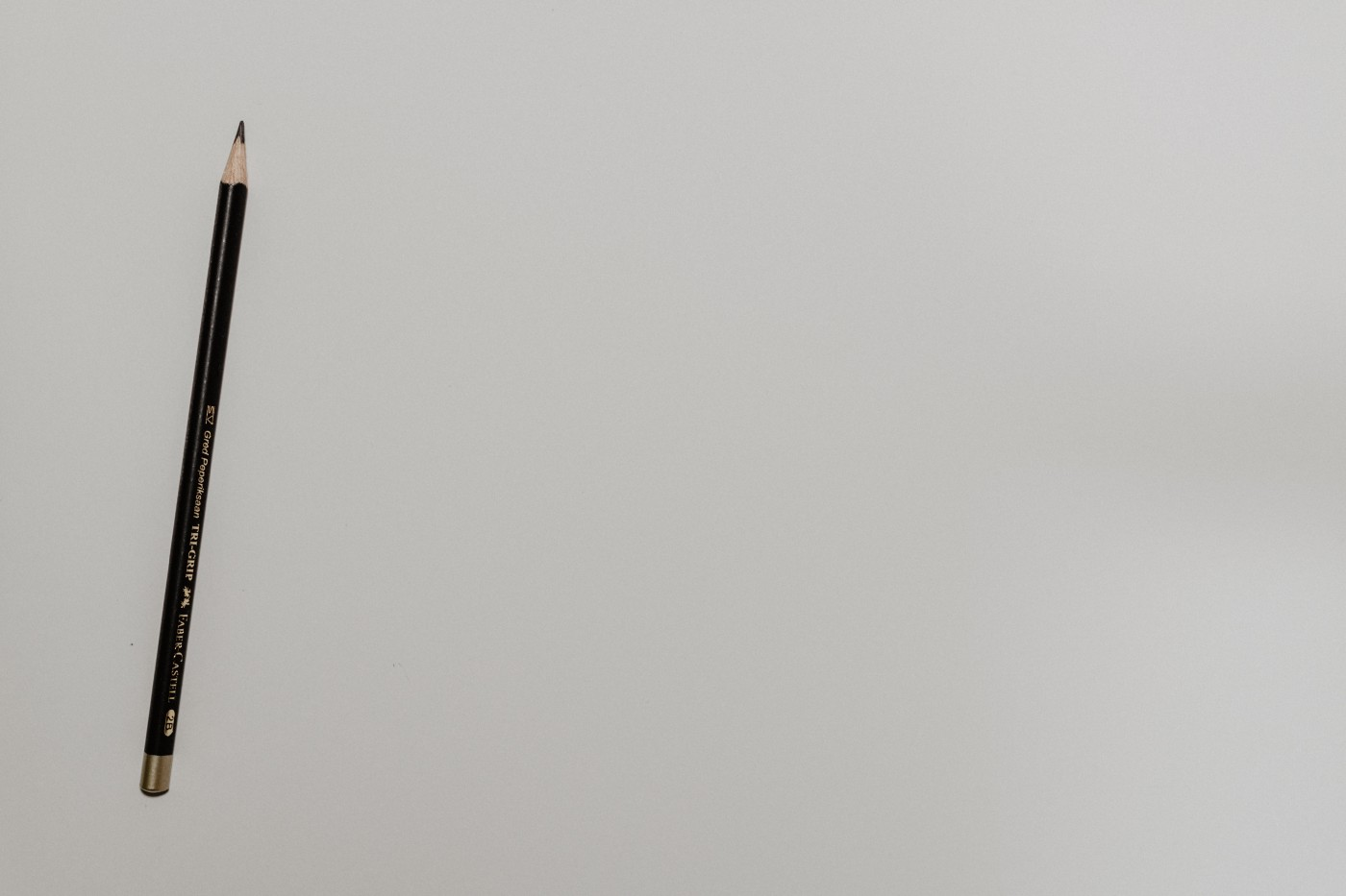 A black pencil on a white background