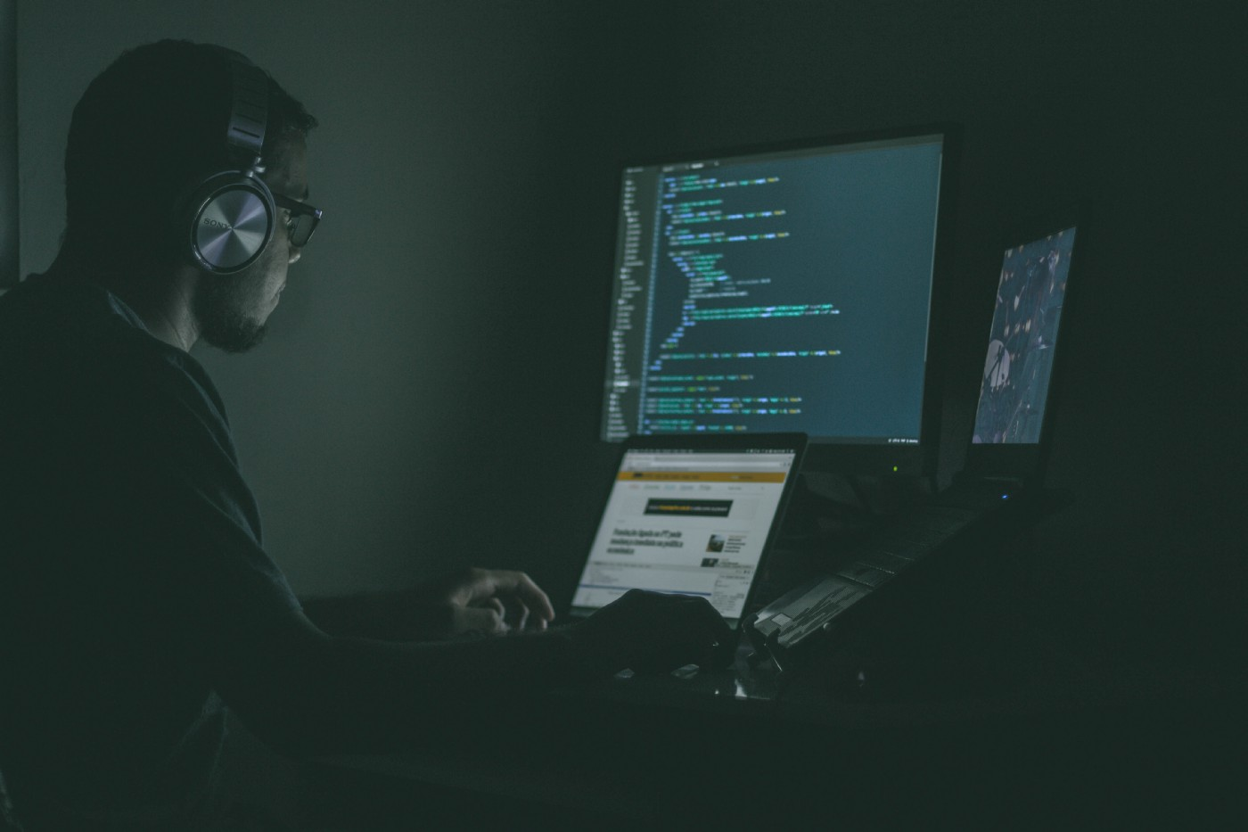 Man coding in a dark room.