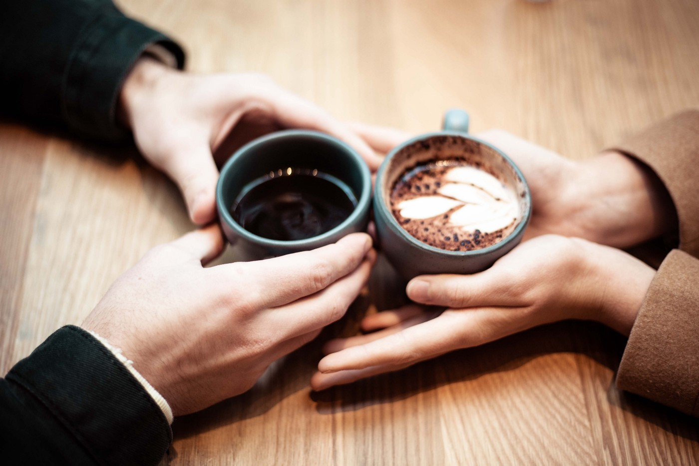 two people's hands holding coffee cups with their hands touching, as if on a date.
