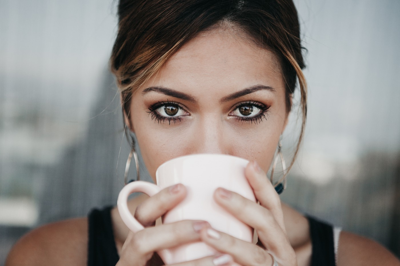 A Brunette with big brown eyes looking straight into the camera sipping coffee from a pink mug