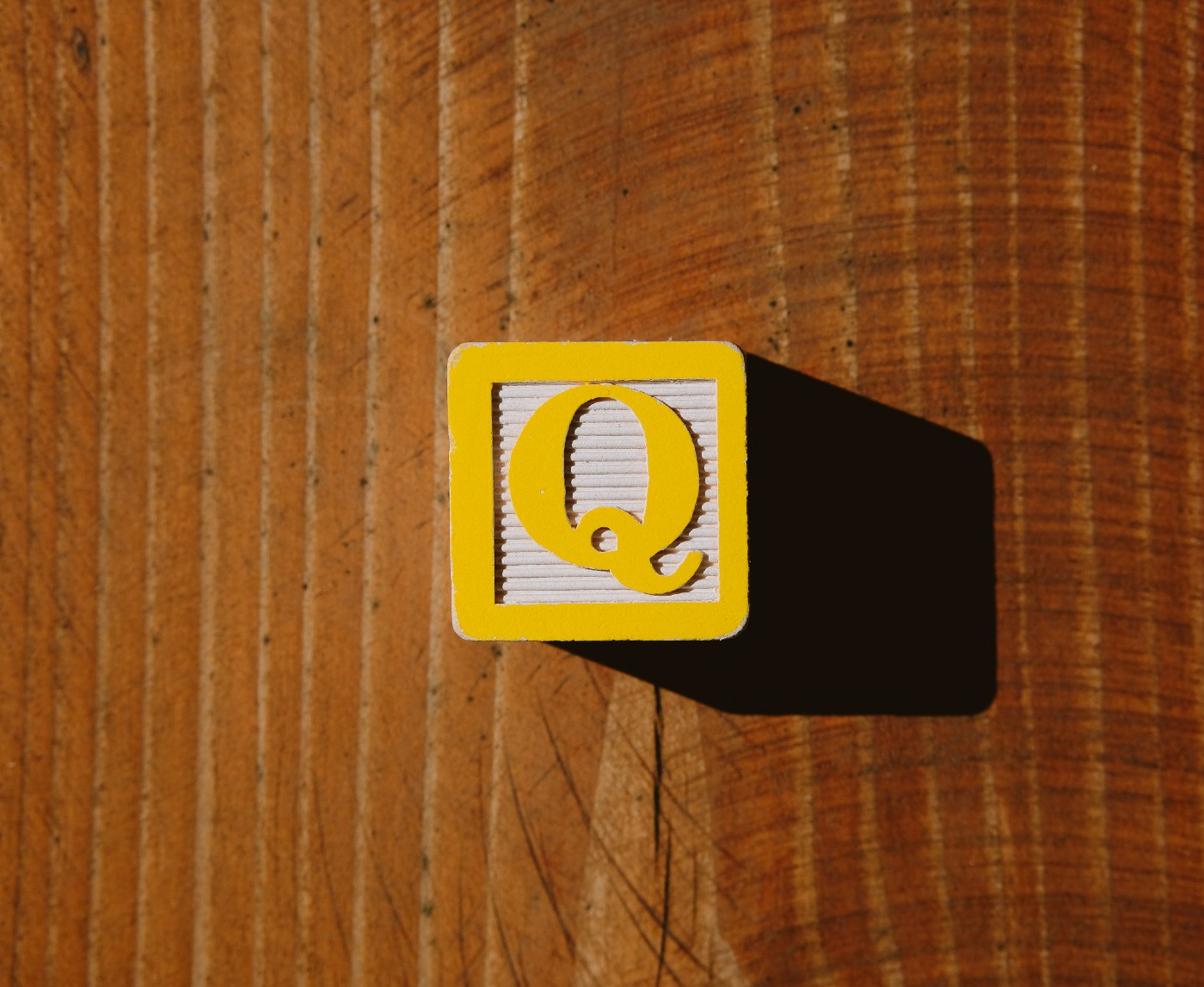 A yellow plastic block with the QAnon logo