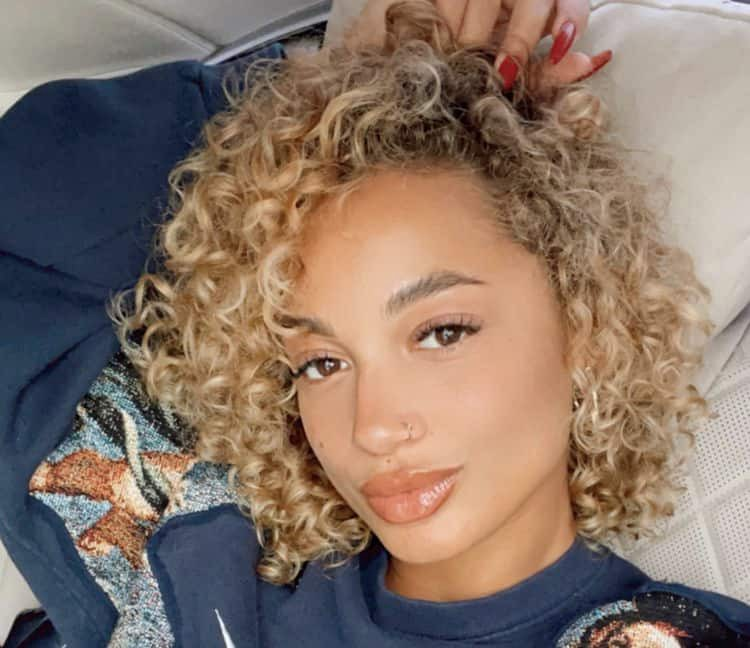 Singer Danileigh looks at camera. Her hair is in a curly twistout.