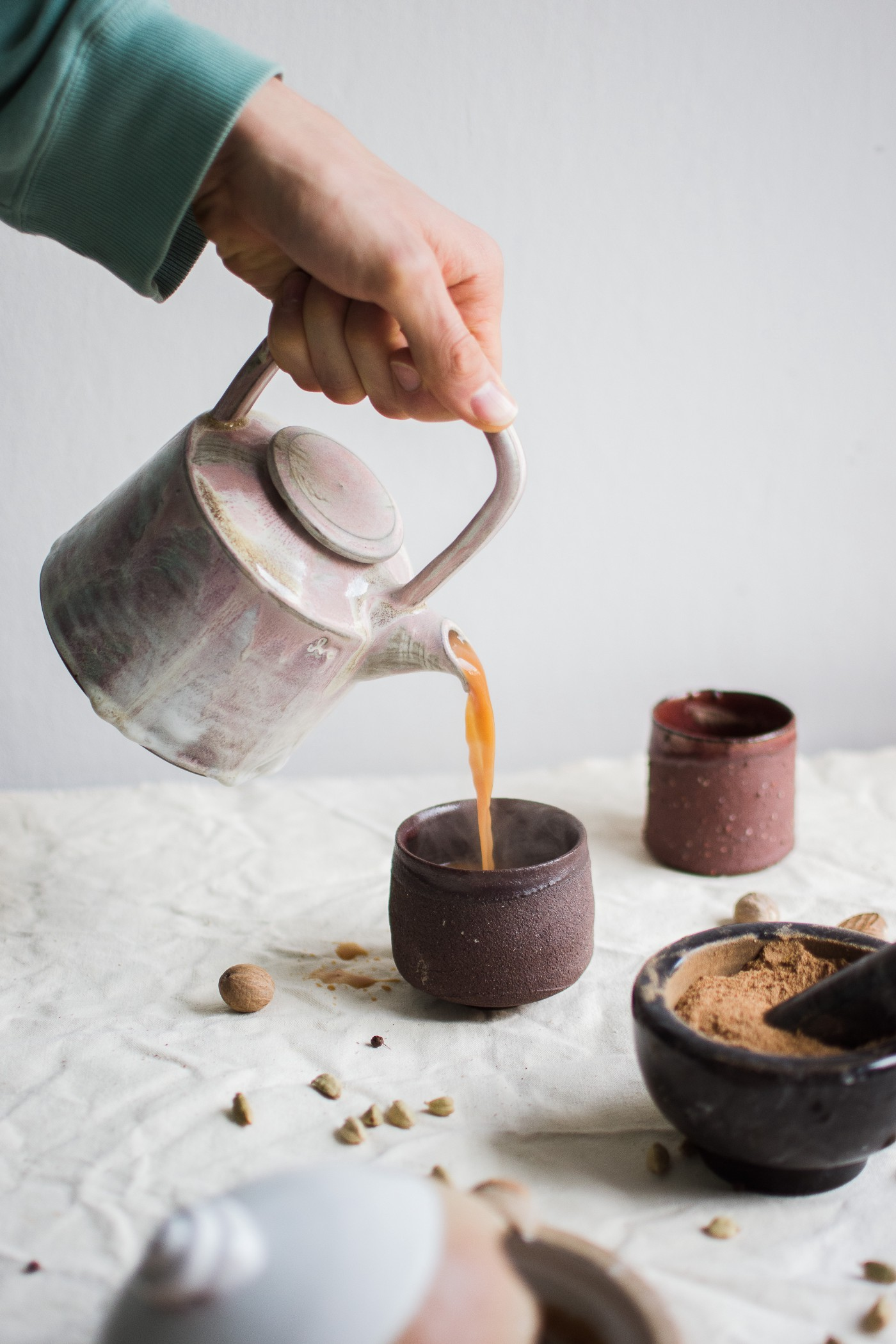 two ceramic cups with a person pouring tea into one cup, nutmeg, bowl of ground nutmeg. How Tea Emerged into Corners of the Globe Via the China Seas by Nancy Blackman. tea. tea drinking. history of tea. herbs. herbal. china. india. england