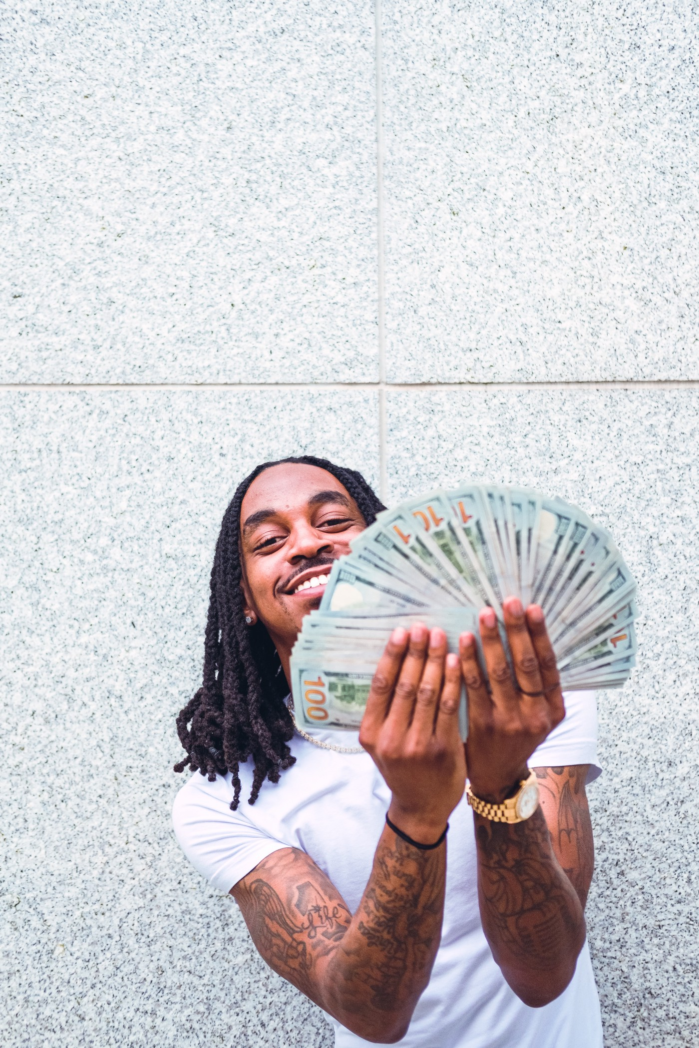 Attractive Black man with braided locs smiles while holding hundred dollars bills like a fan