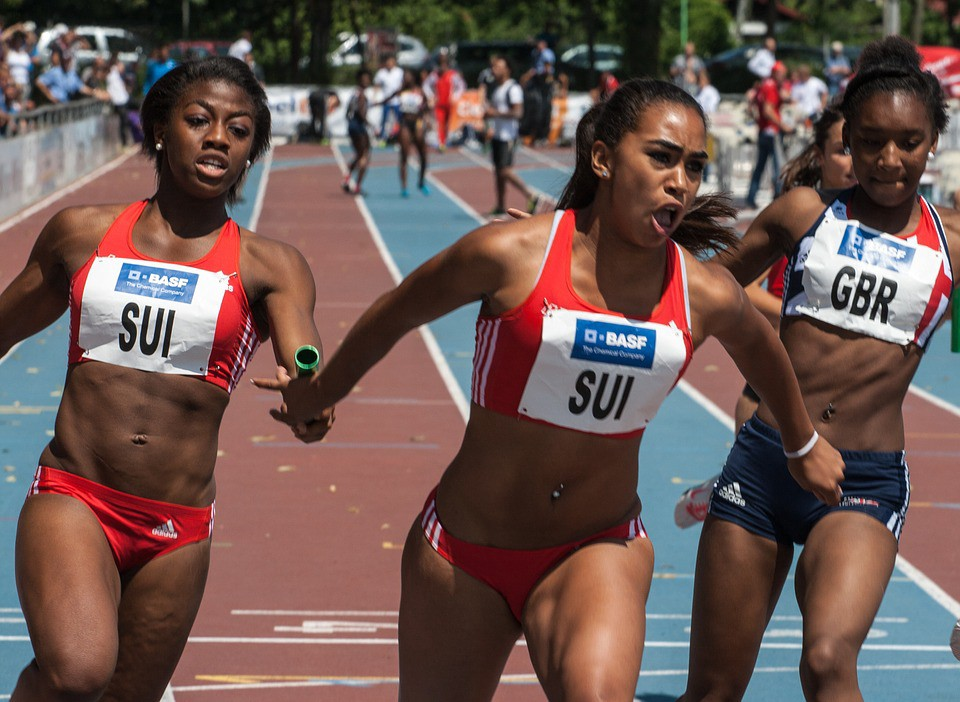 Black female relay runners passing the baton in a track and field race.