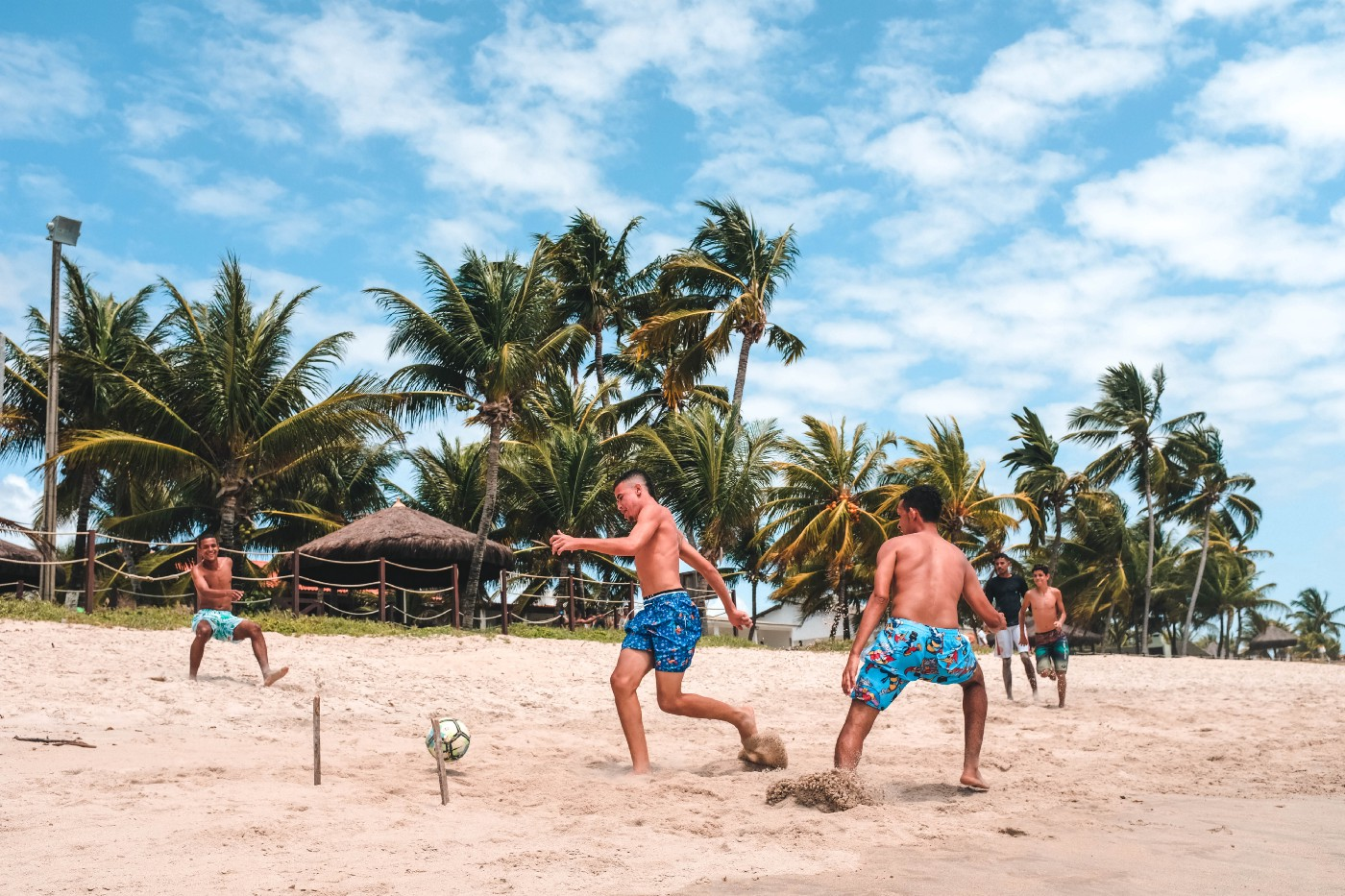 Young men playing soccer on a beach in Brazil.