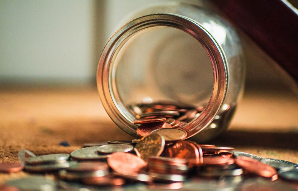 Photo of a glass jar spilling out coins.