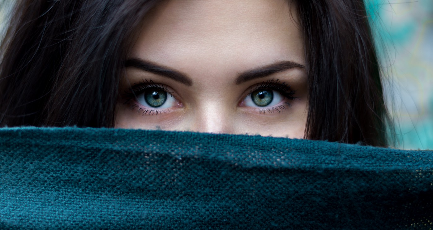 Close up of a young brunette with pretty green eyes peaking over the edge of a dark blue blanket
