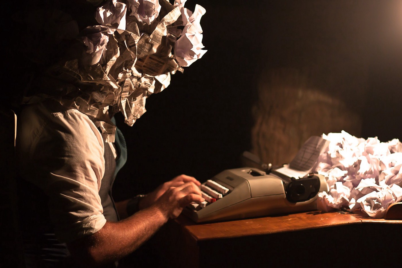 Quirky photo symbolizing writer's block. Person sitting at typewriter with a bunch of crumpled paper.