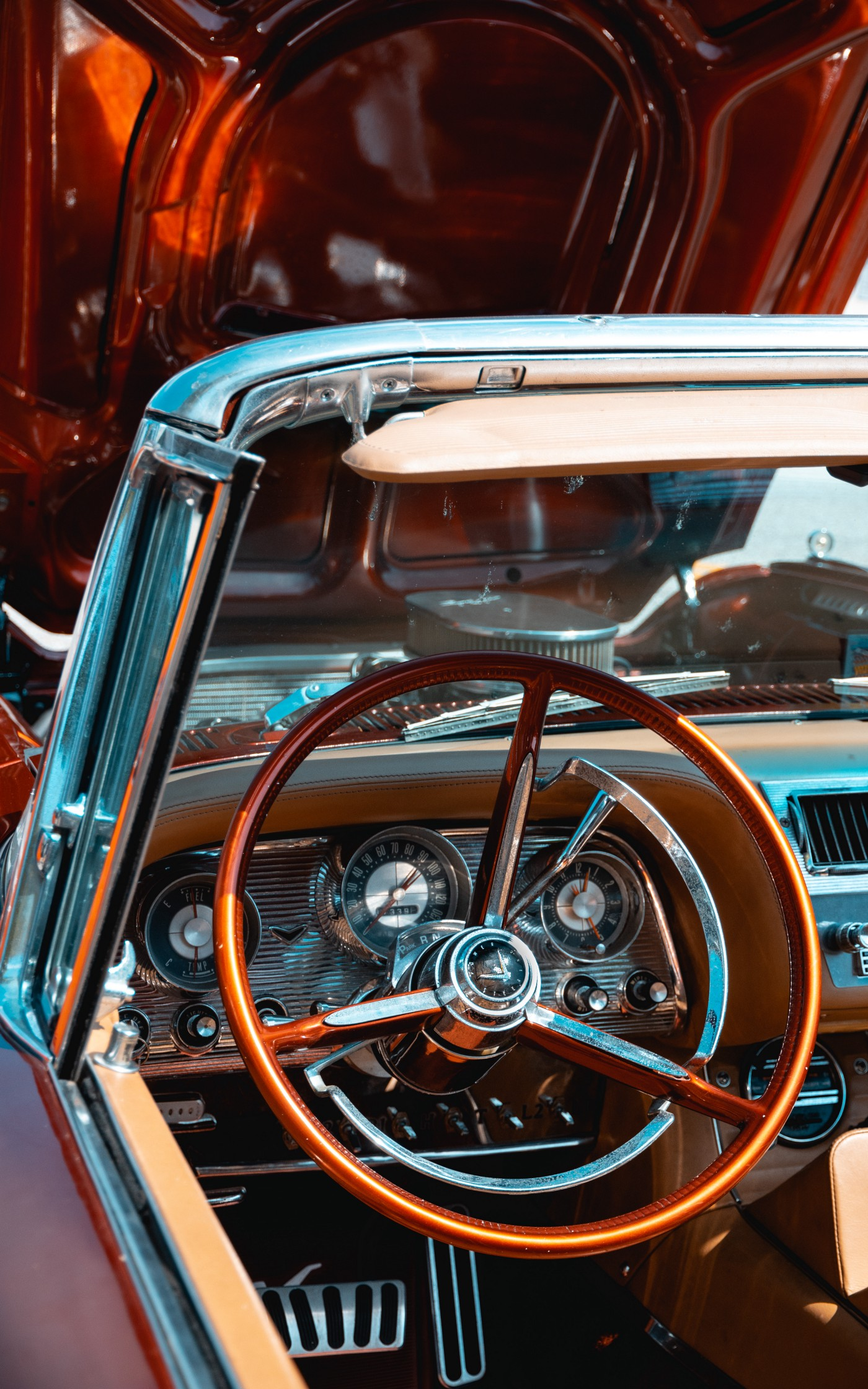 Vintage car shot at driver's seat with old style steering wheel and dash and hood opened up from inwards out.