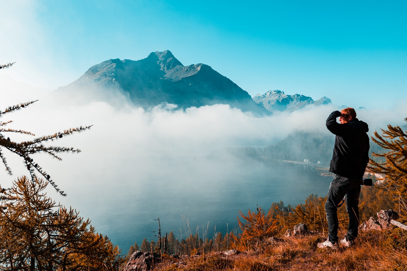 Man looking across valley at mountains