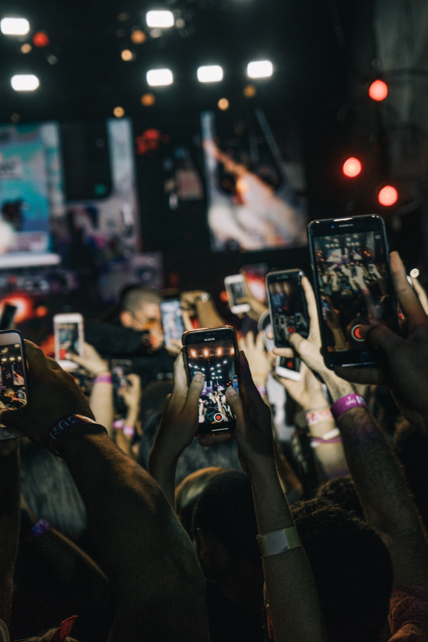 A mass of phones being held up in the air at a venue to post on social media.