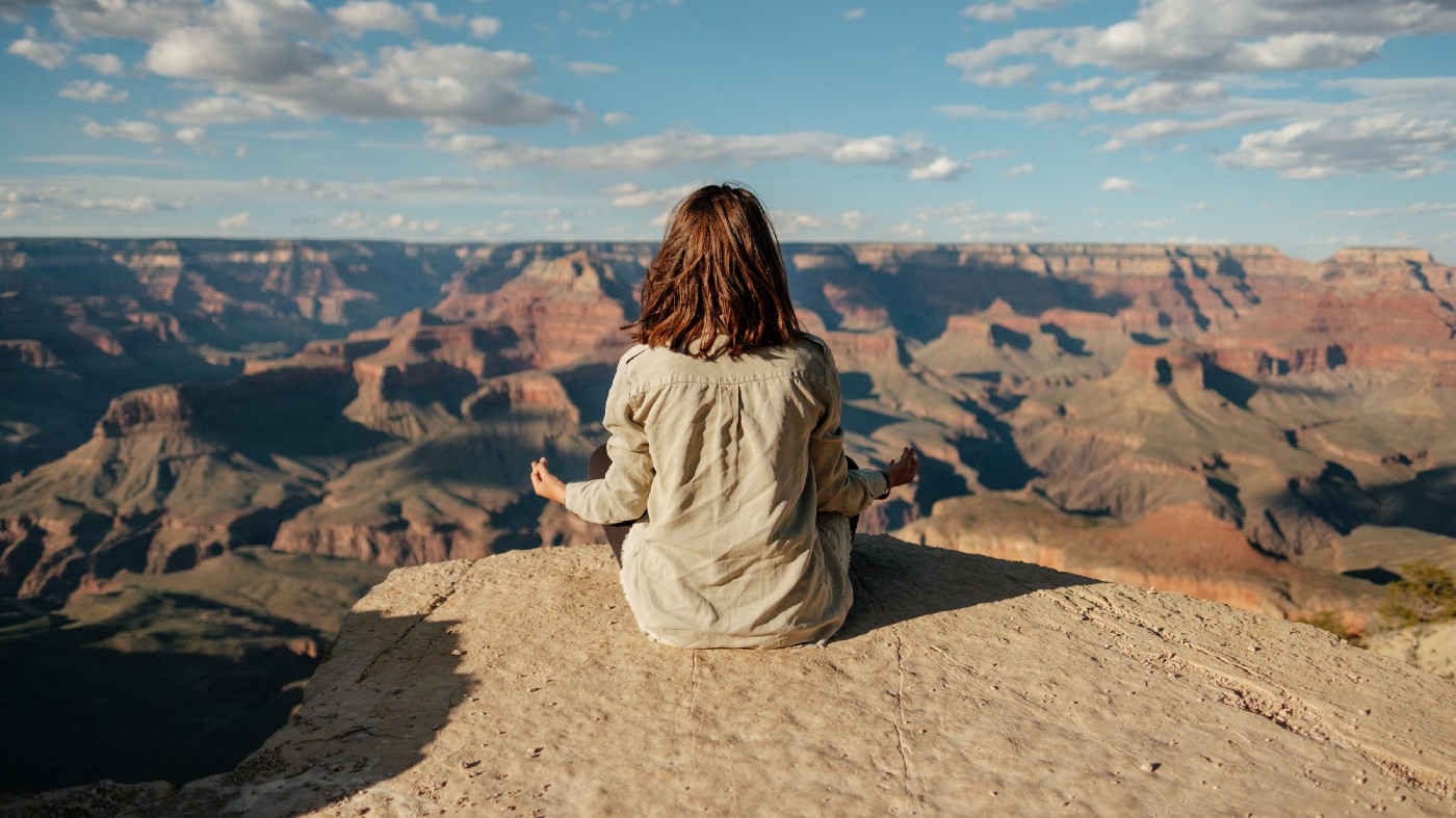 Afternoon meditation at the Grand Canyon. Woman sits cross-legged on a rocky ledge with unobstructed view of the canyon formations.