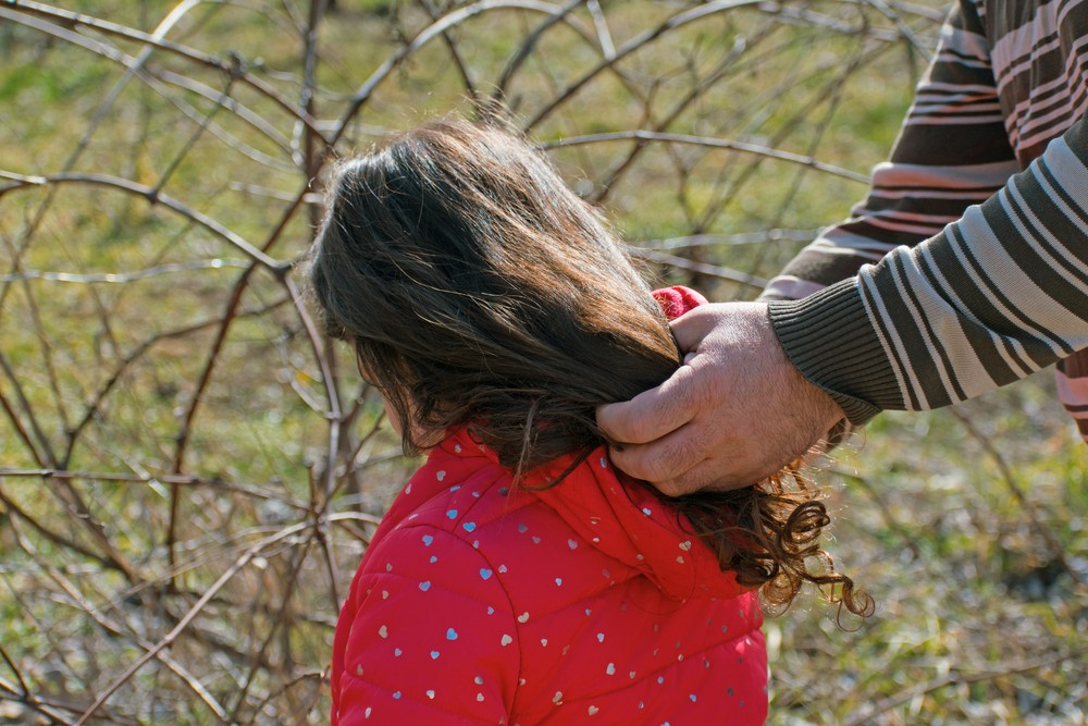 Man's hands on the hair of a little girl to indicate child sex abuse. Sexual activities need not always involve the genitals.