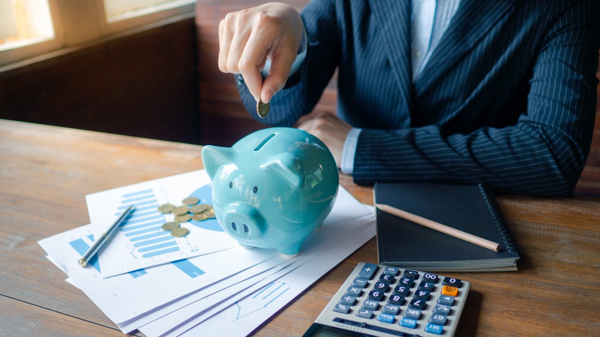 A person in a blue striped suit sits at a desk with a book, pencil, calculator, coins and paper, with a light blue piggy bank on top of the papers, putting a coin into the piggy bank.