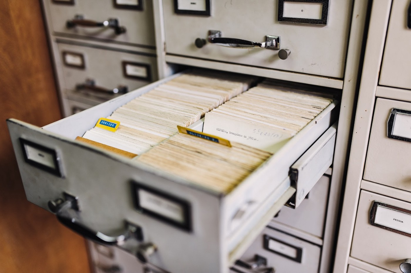 A filing cabinet with an open drawer with many index cards inside.