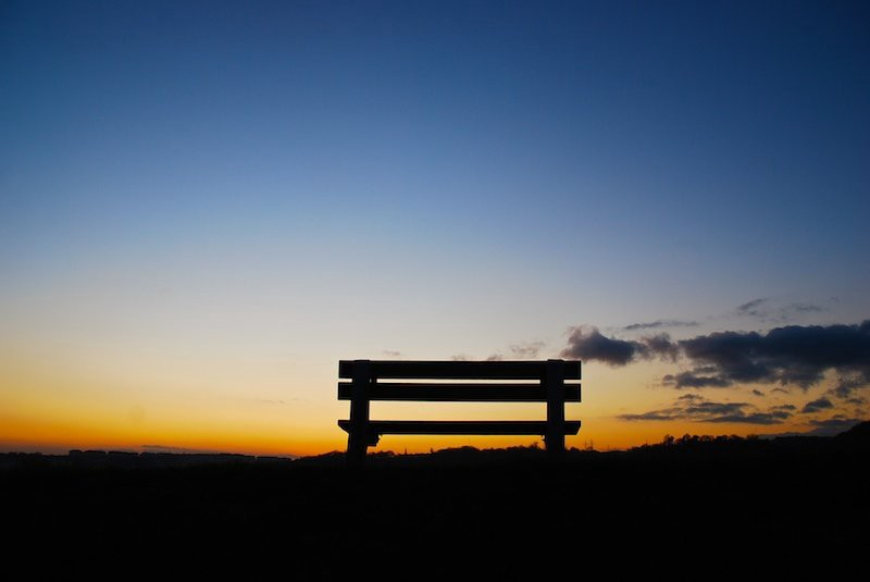 A silhouette of an empty bench in a grassy field at sunset.