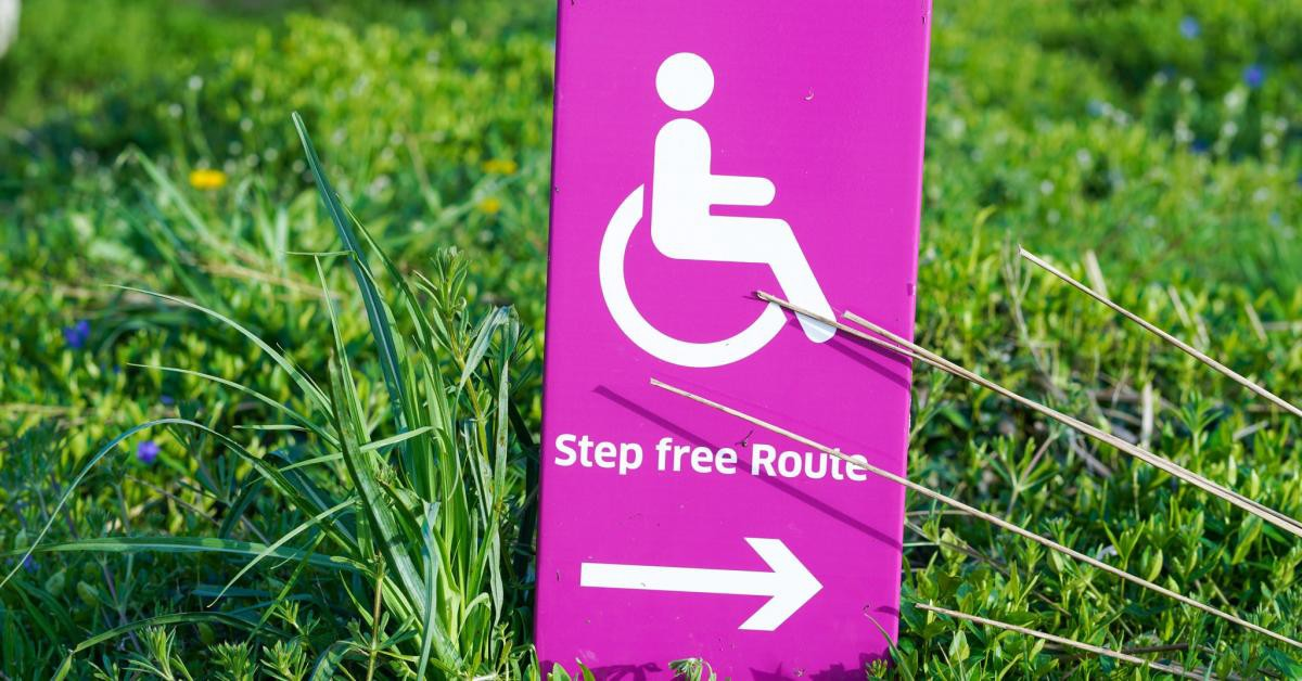 Pink sign in the grass reading Step free rout with an arrow pointing to the right