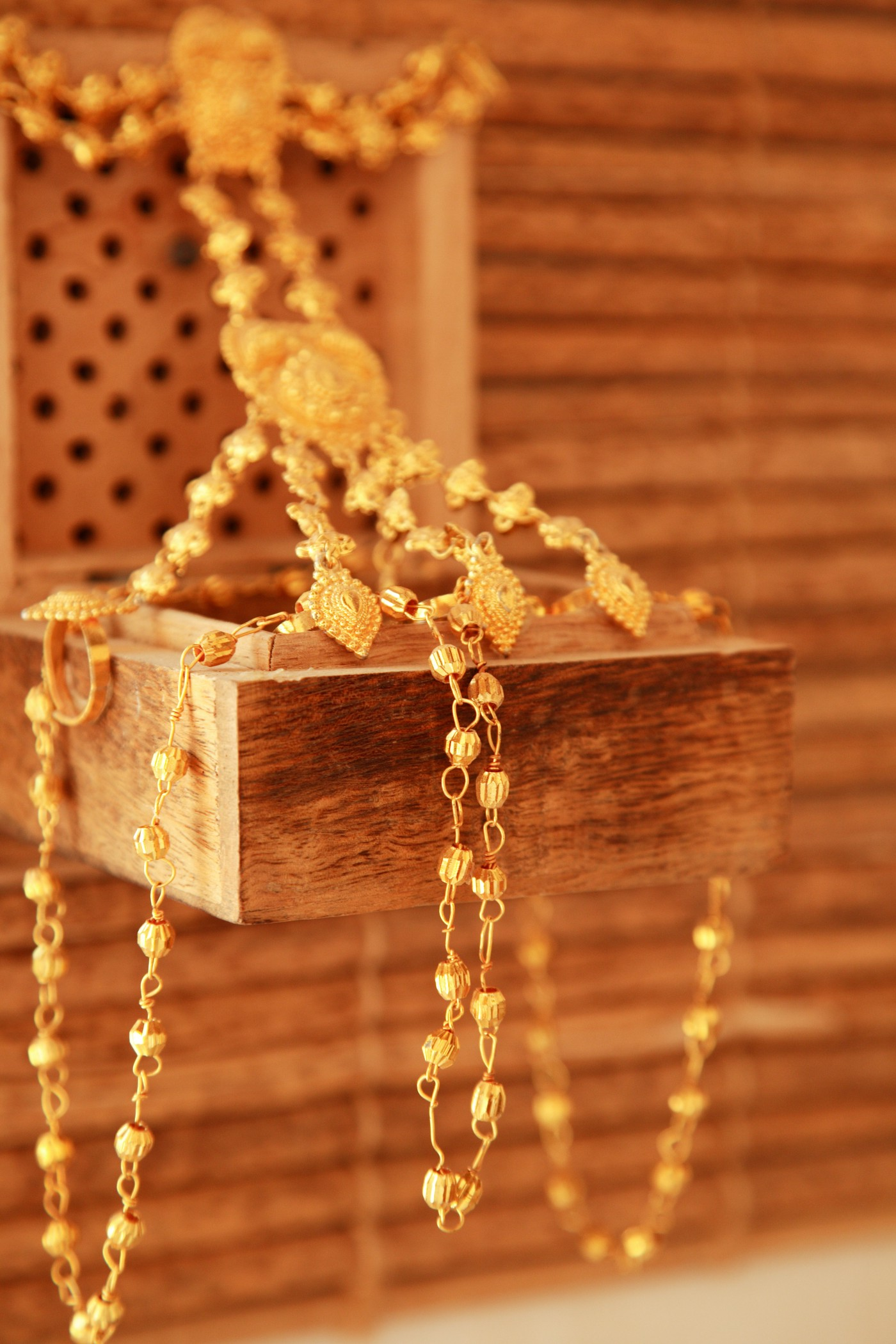the image is that of a jewelry box built into a board wall with long gold pieces of necklaces draped all over.