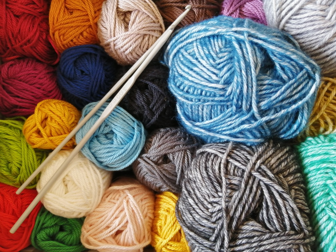 box full of balled-up yarns of different sizes and colors and two knitting needles
