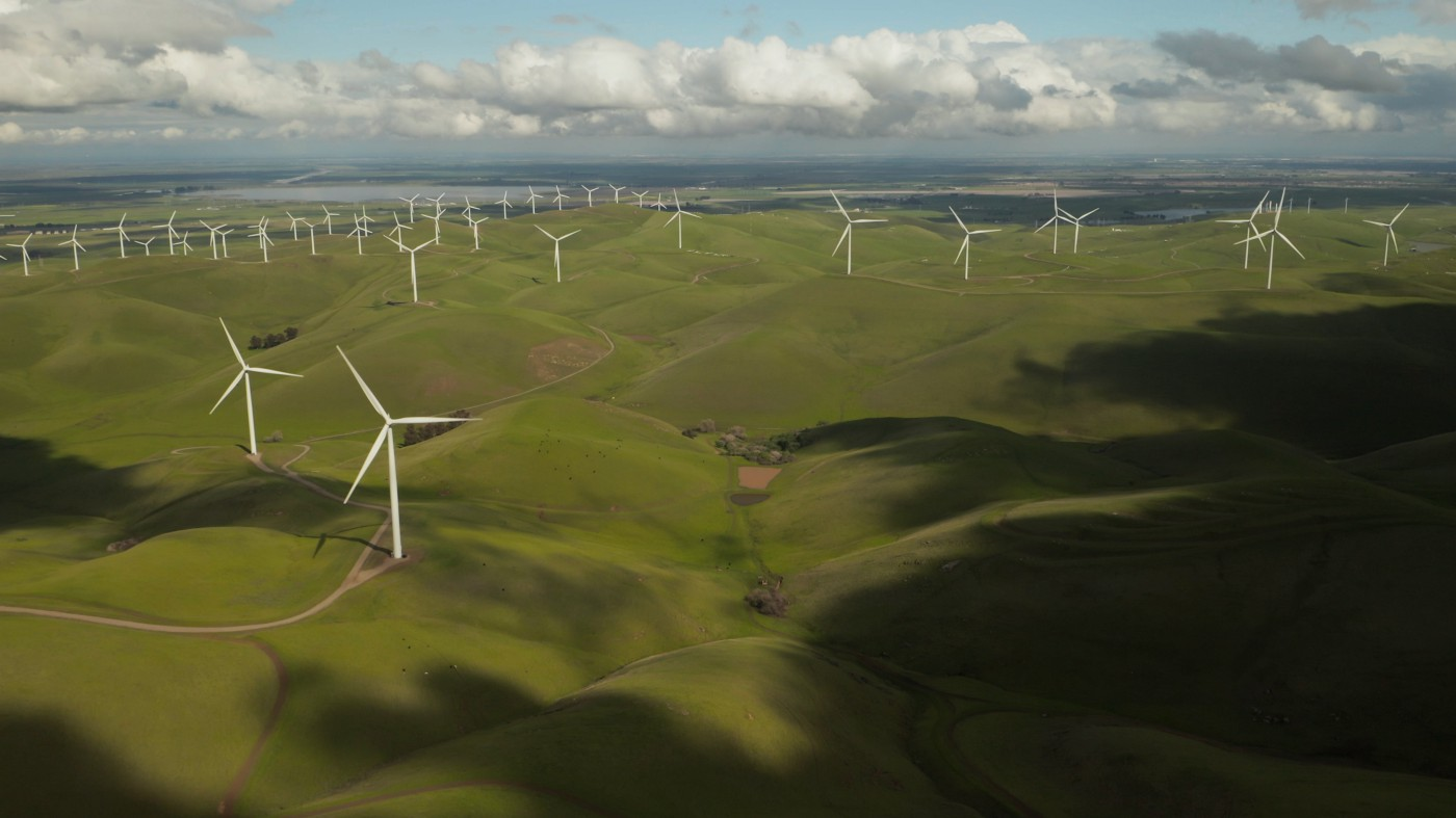 A shot of a wind farm with lush, green meadows.