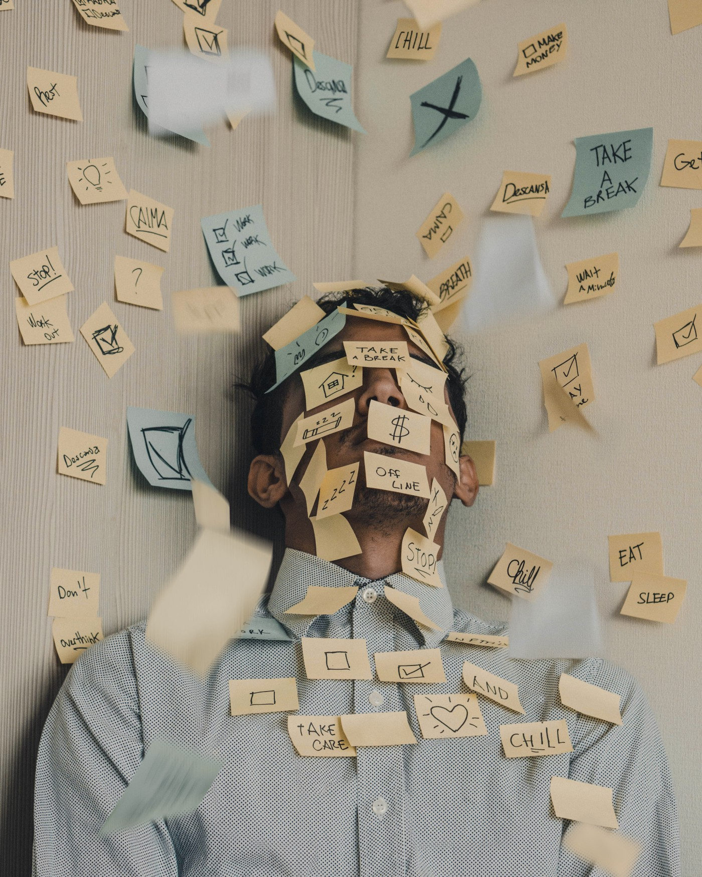 An overwhelmed male with post-it notes all over his face at work