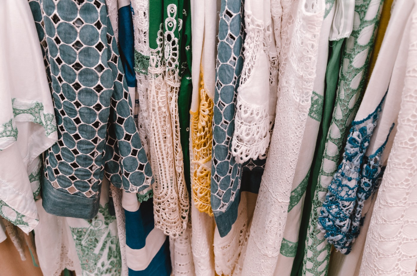 A selection of lacy, loose, and white garments with cool-colored accents and patterns on a rack