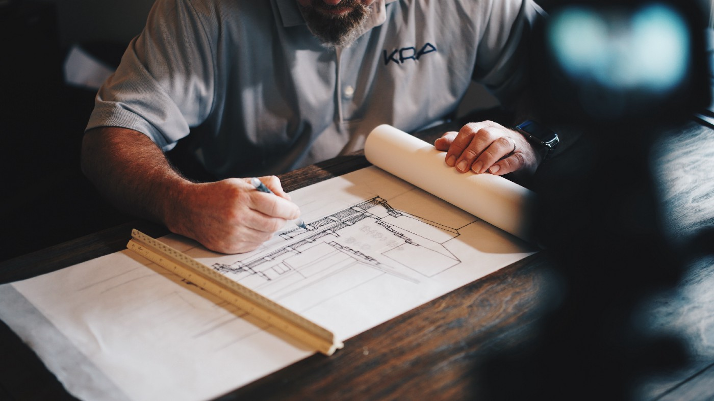 A male architect with a blue shirt sitting on a wooden desk with a constructional drawing in front of him.