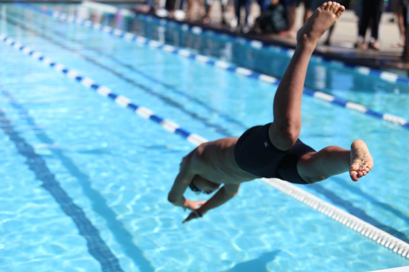 A man diving into a pool. The picture should symbolize a person which is ready to start developing a web application.