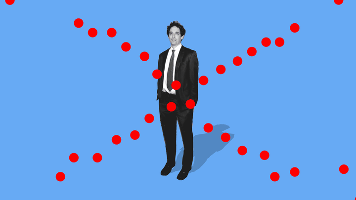 A full-length black-and-white pic of Alex Berenson, in a suit and tie, on a solid blue background. Red dots have been overlaid to create a large X centered on his stomach.