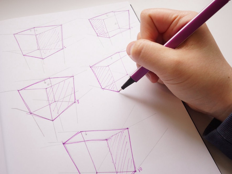 A closeup of my hand drawing on a sketchbook. In the sketchbook are 3D boxes I am practicing.