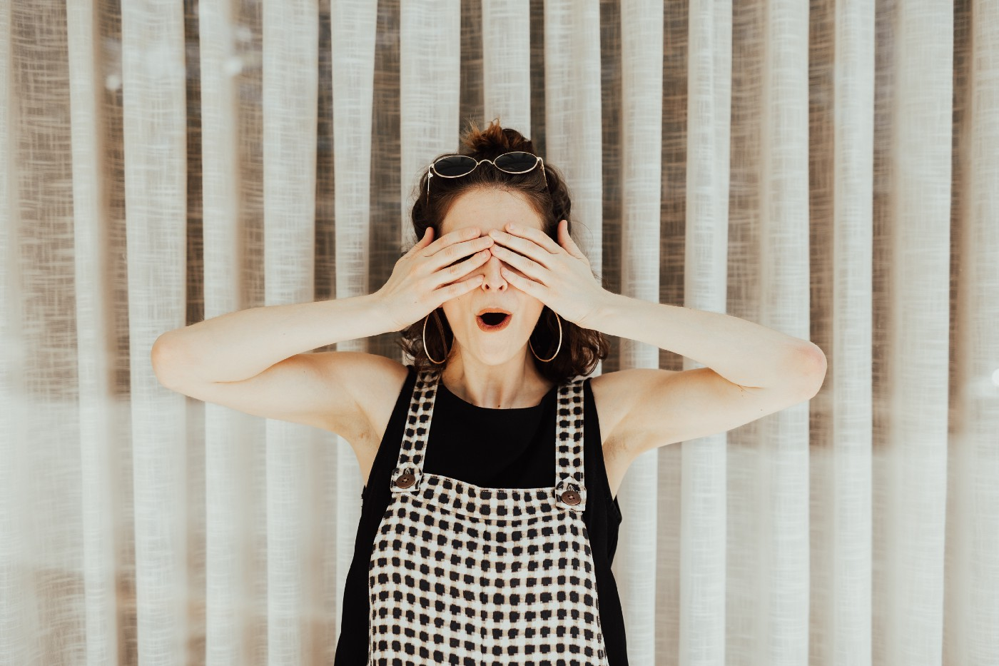 Woman covering her eyes and looking surprised