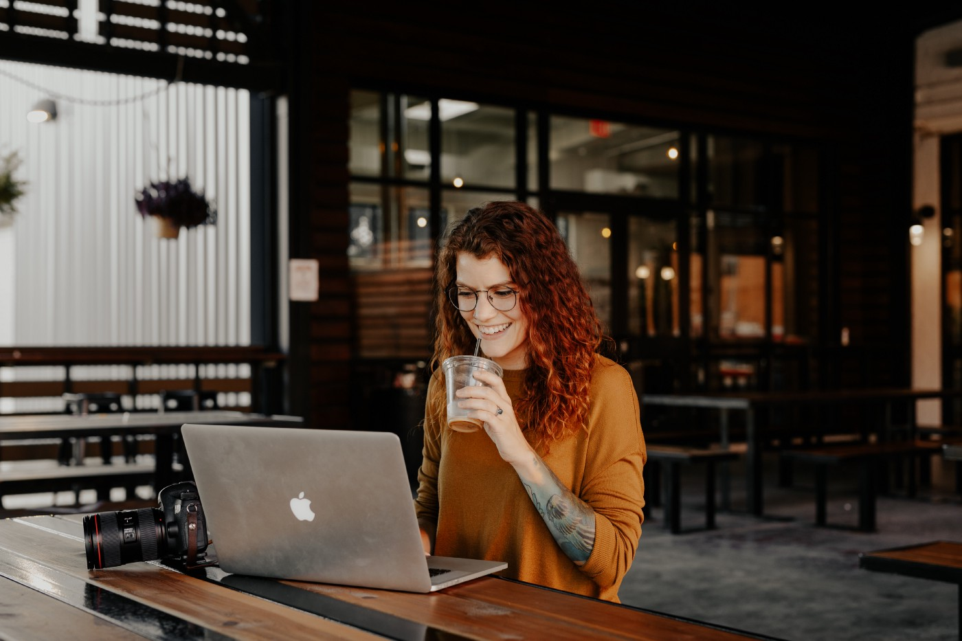 Woman sitting at a bench, working on her computer with a drink in hand