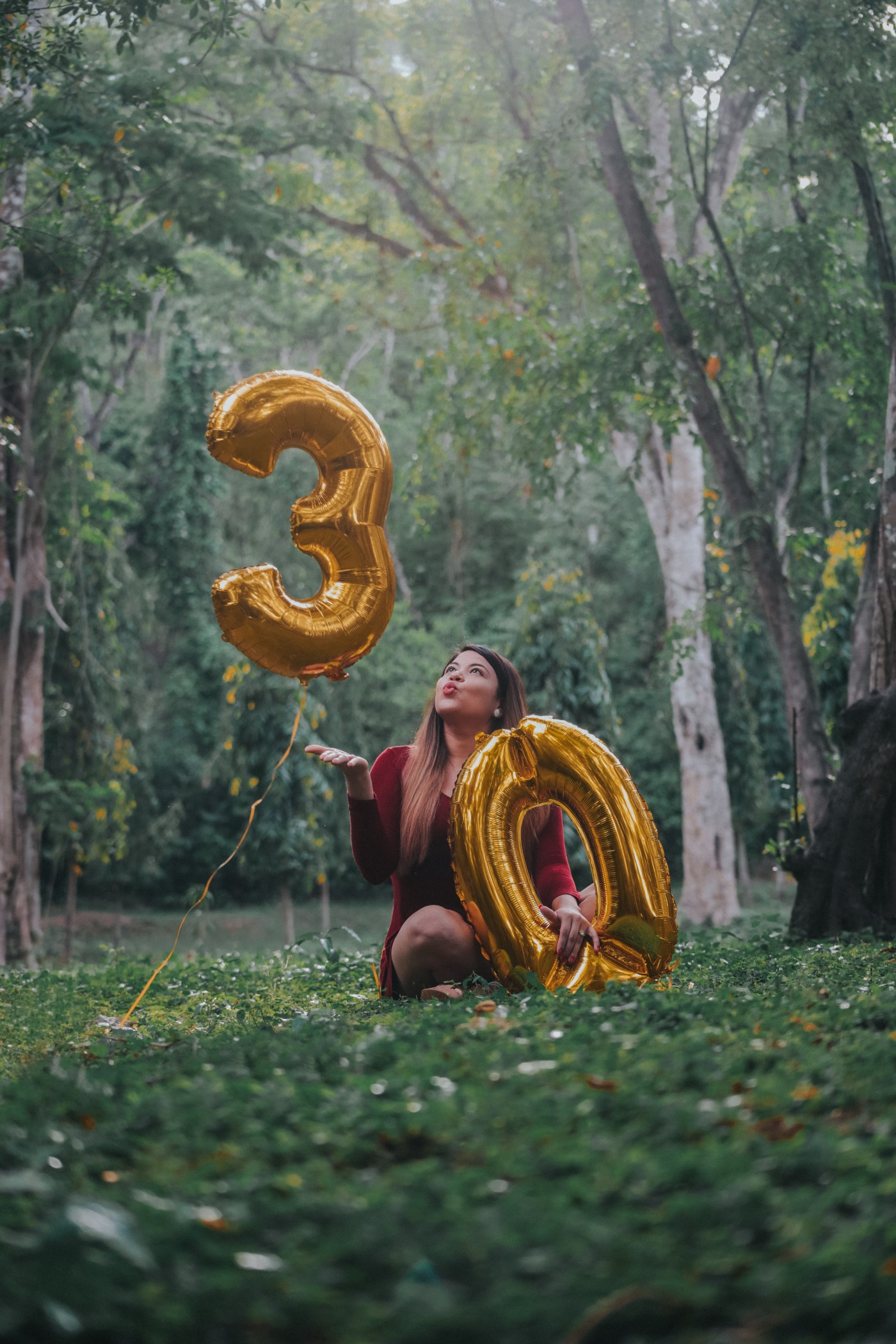 Female in red dress in a forested area with two golden balloons, one 3 and one 0. She's airkissing the 3.
