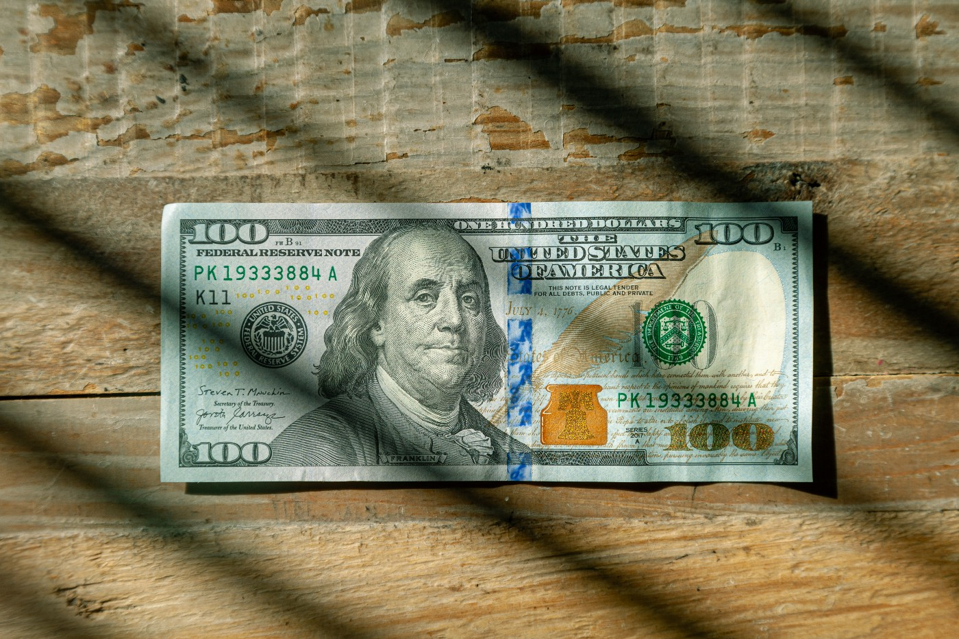 100 dollar bill on a wooden table with diagonal strips of light.