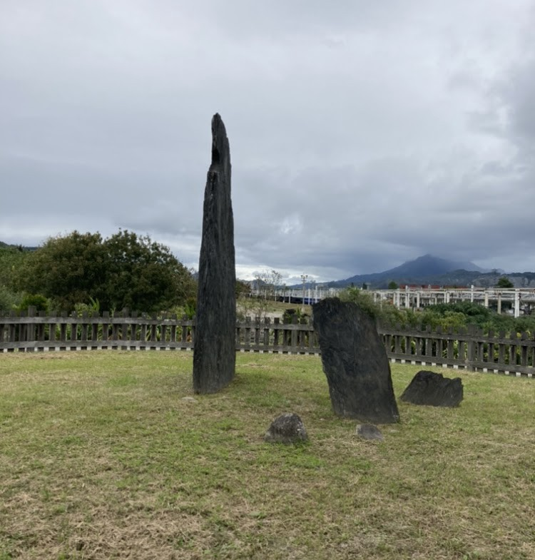 An ancient tombstone dated back 5300 years stands tall against a Southern Taiwan mountain skyline on a cloudy January in 2021
