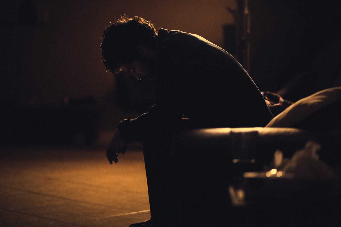 In a room without much light, a man sits on a couch with his arms resting on his legs, his eyes closed, and his head bowed.