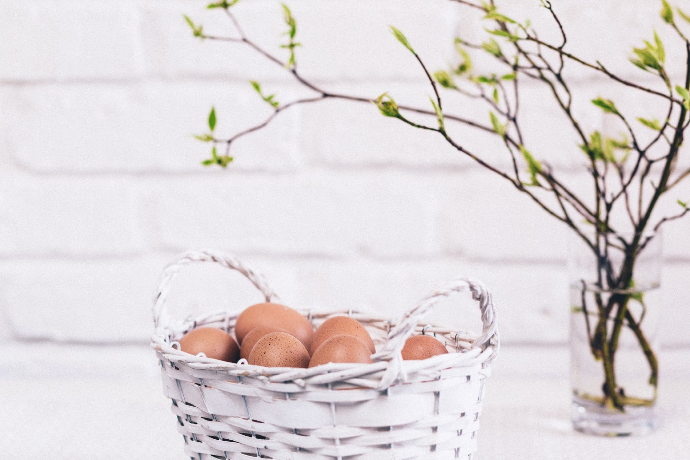 a basket of eggs beside a vase of sprouting branches