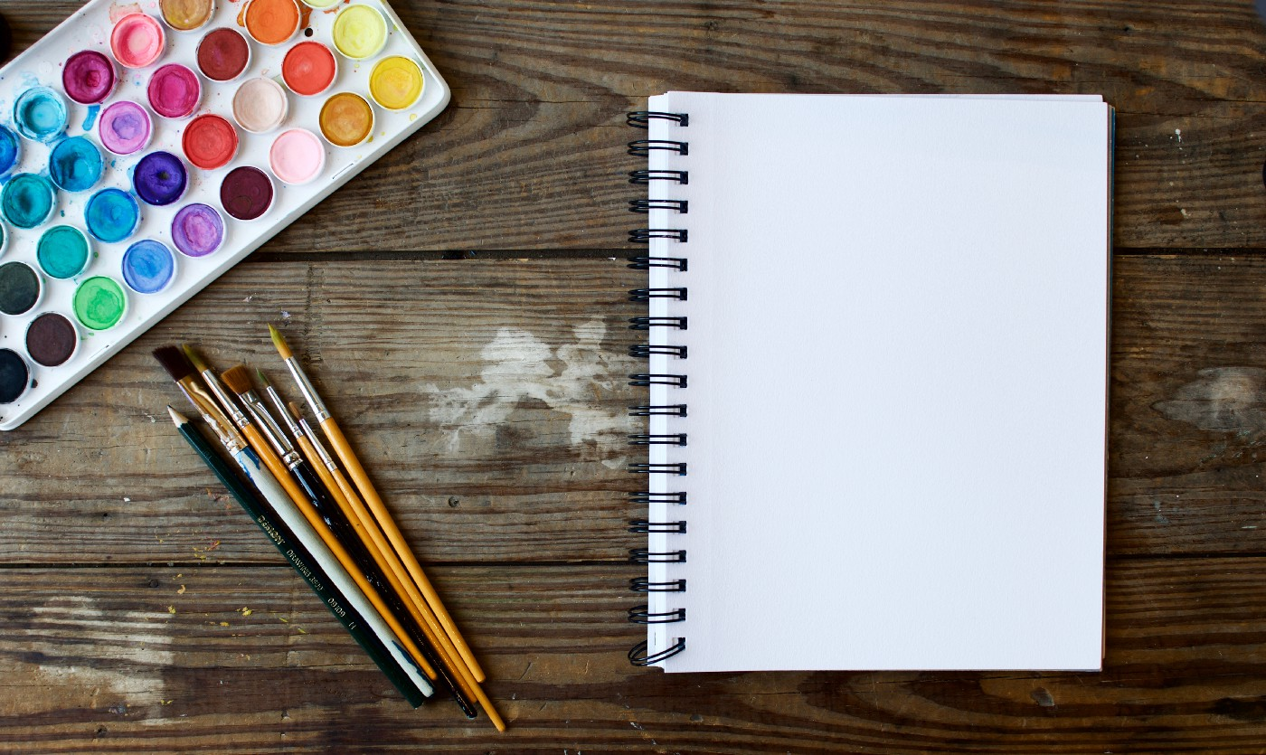 Paint brushes and a blank notebook