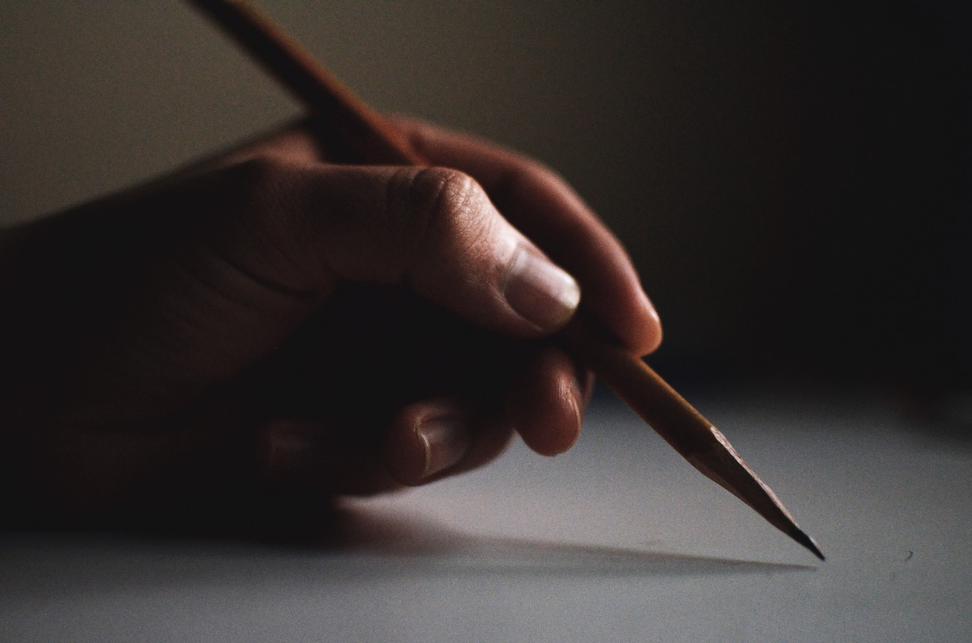 photo of a woman's hand holding a sharpened pencil