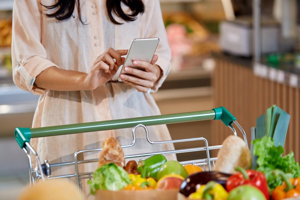 woman holding smart phone standing next to basket full of vegetables and healthy super food while shopping in the supermarket to indicate smart shopping