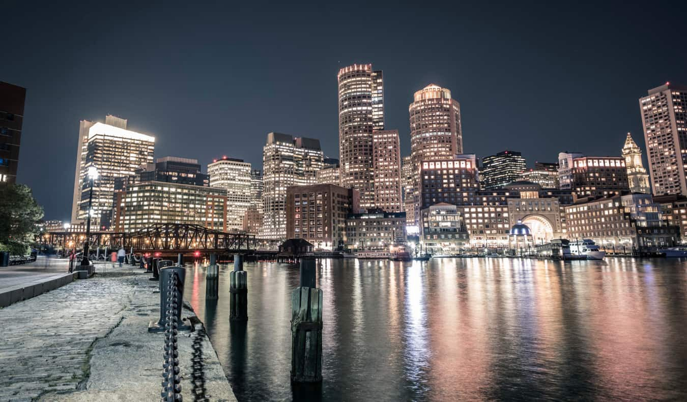 The skyline of Boston lit up at night by the water