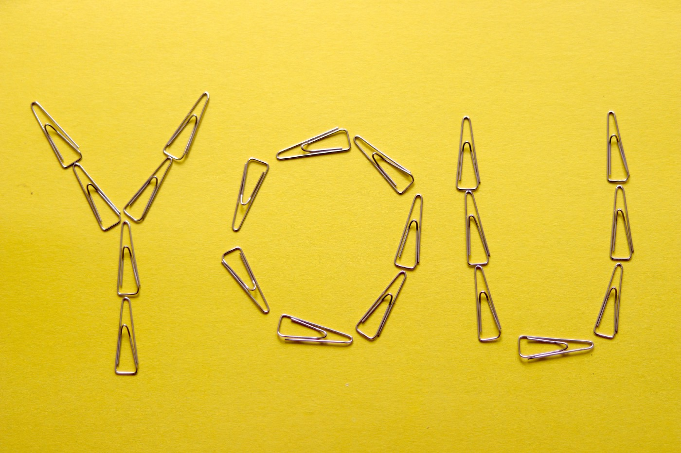 """The word """"You"""" spelled out with paper clips on a yellow background."""